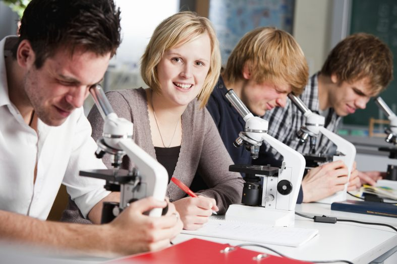 Students with microscopes in biology class