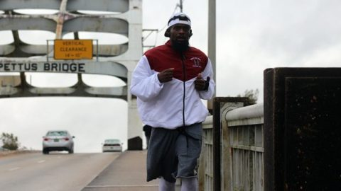 Band Director Matthew Goodman runs across the Pettus Bridge