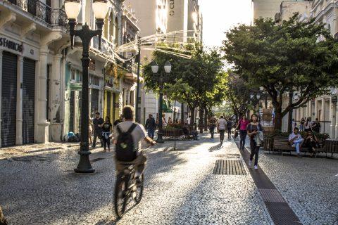 Man biking down cobbled road of pedestrians