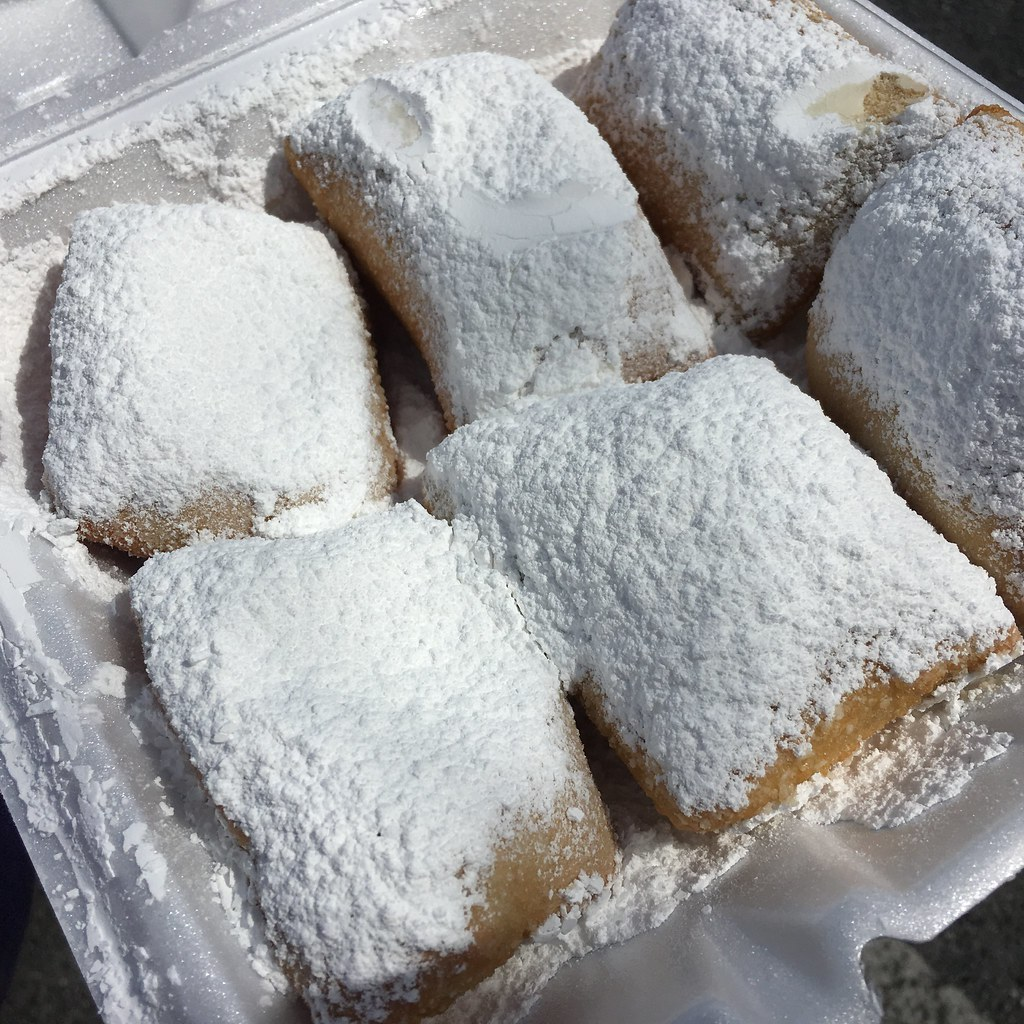 Photo of powdered sugar covered beignets in a box