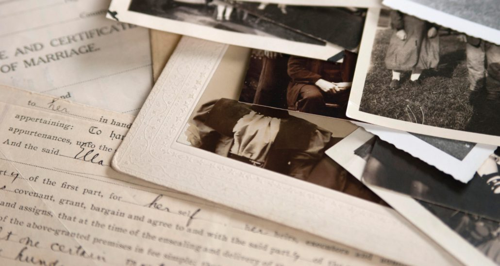 Pile of photographs sitting on top of a handwritten letter