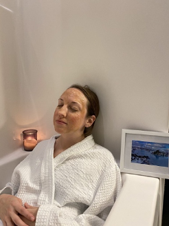 Woman wearing white bathrobe with face mask
