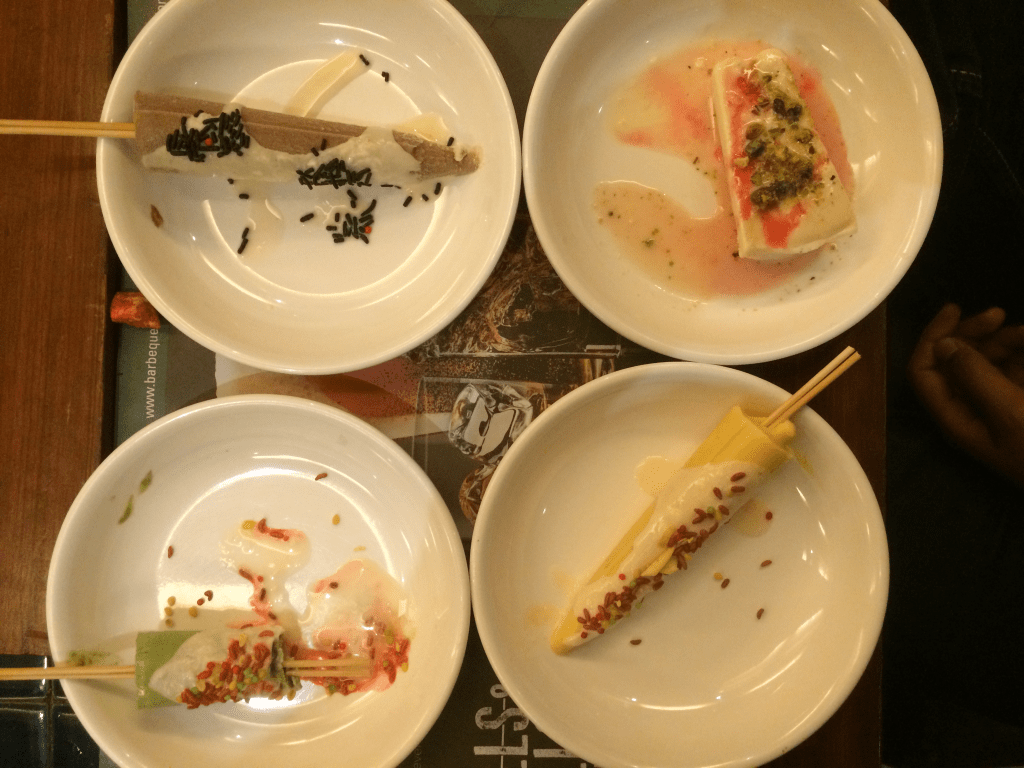 4 plates containing different forms of kulfi