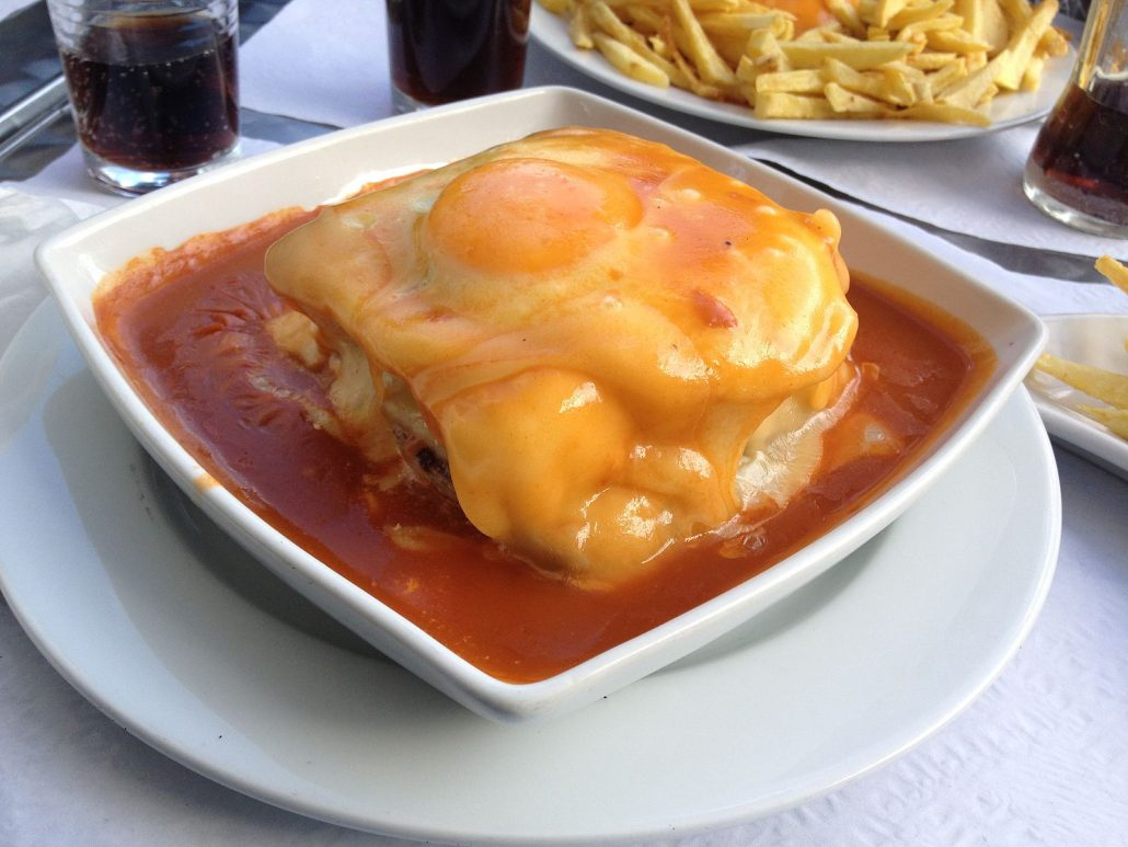 francesinha sandwich topped with an egg