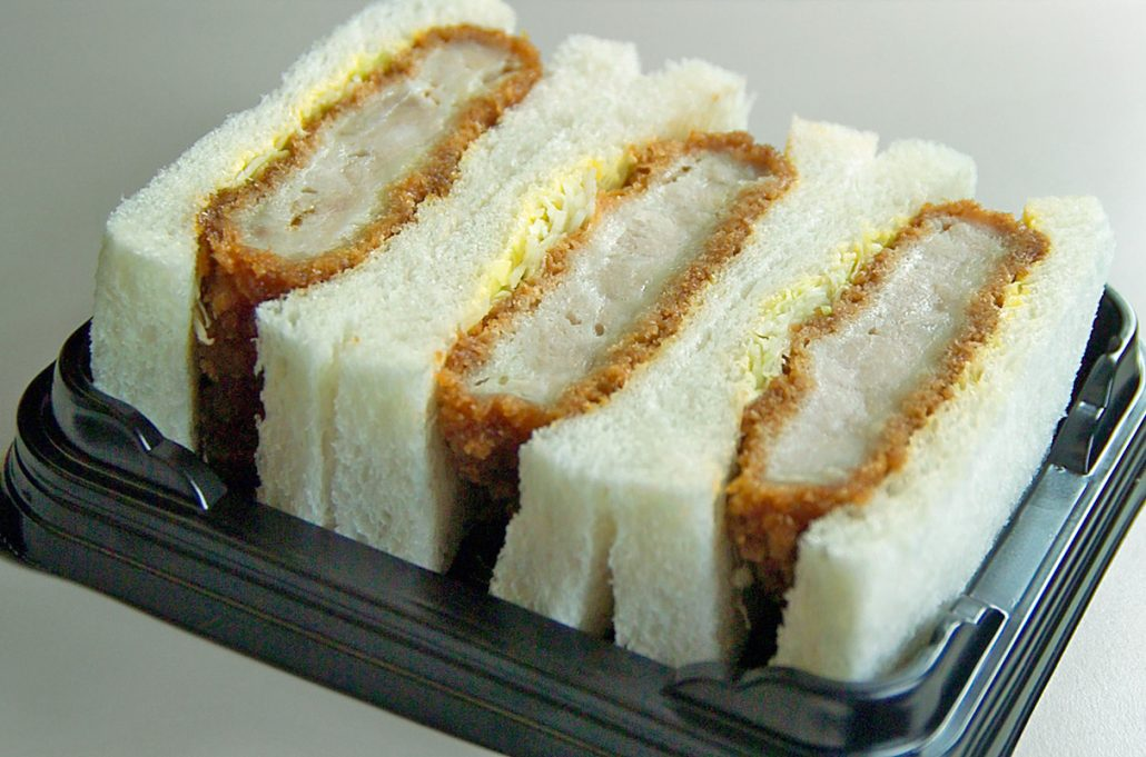 Katsu sando sandwich in container - 3 pieces of white bread, plus a pork cutlet and cabbage