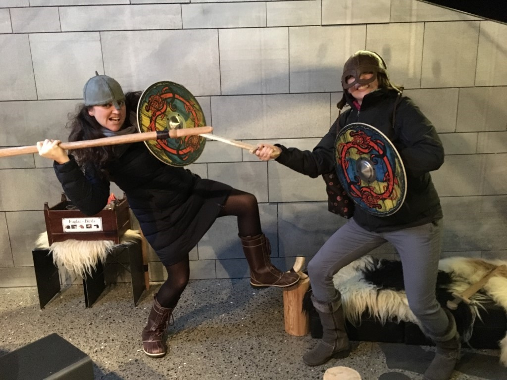 Woman and man holding painted shields and wooden spears like vikings