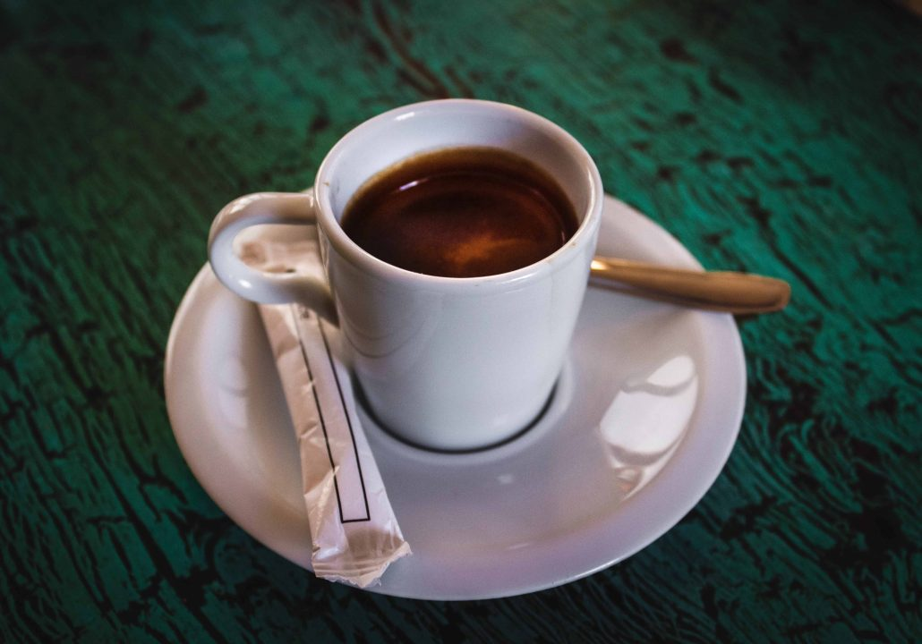 Espresso cup on saucer with sugar tube and spoon