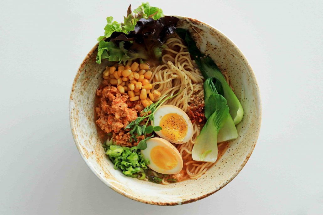 Bowl of ramen containing bok choy, ground meat, corn and marinated egg