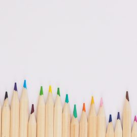 Colored pencils lined up on white background