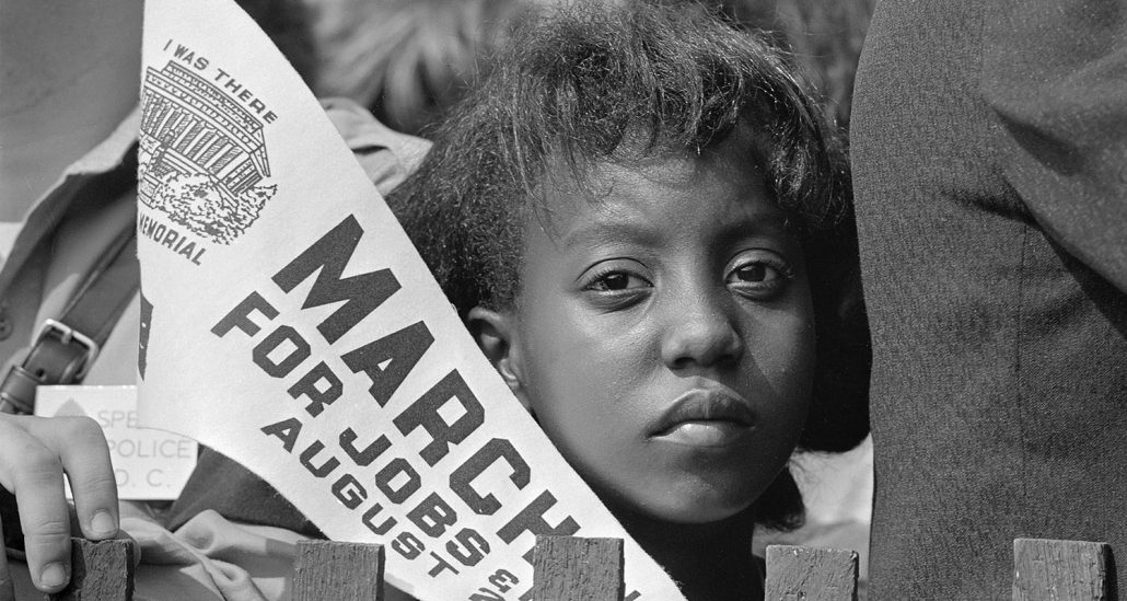 Young Woman holds a banner at Civil Rights March on Washington, D.C. on August 28, 1963