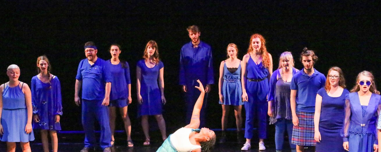 Dancers dressed in bright blue surround a girl dressed with light green and white